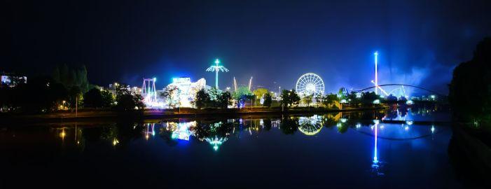 Bild: Straßenfest mit leuchtenden Attraktionen und einem leuchtenden Teufelsrad.